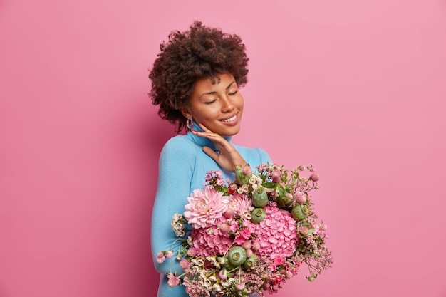 Charming young woman with gentle smile, touches face, stands indoor, keeps eyes closed, receives bouquet of flowers from colleagues in honor of her promotion, models