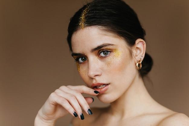 Affascinante giovane donna con orecchini d'oro. foto del primo piano della ragazza dai capelli neri allegra in piedi sulla parete marrone.