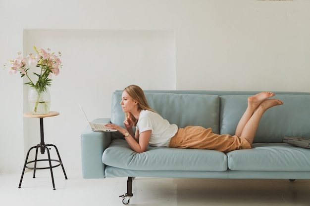 Charming young woman with laptop working at home while sitting on sofa