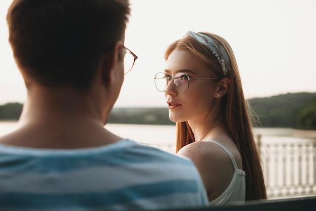 公園のビーチに座っている間、屋外で彼女のボーイフレンドと話している赤い髪とそばかすを持つ魅力的な若い女性。