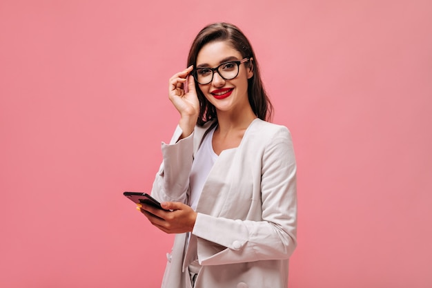 Charming young woman with red lips in beige outfit and eyeglasses looks into camera and holds smartphone on isolated pink background.