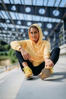 Очаровательная молодая женщина со стройным телом, отдыхая на открытом воздухе после тяжелой тренировки.