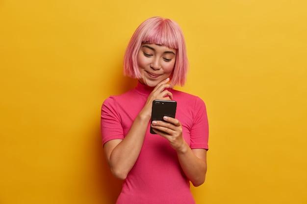 Affascinante giovane donna con acconciatura alla moda, sorride piacevolmente guardando smartphone