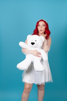 Charming young woman woman hugging a big white teddy bear and blowing a kiss