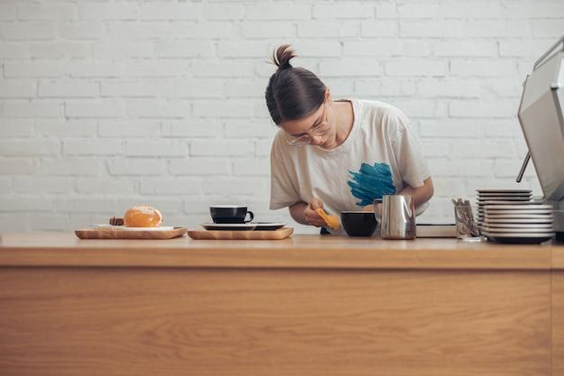 커피숍에서 일하는 매력적인 젊은 여성