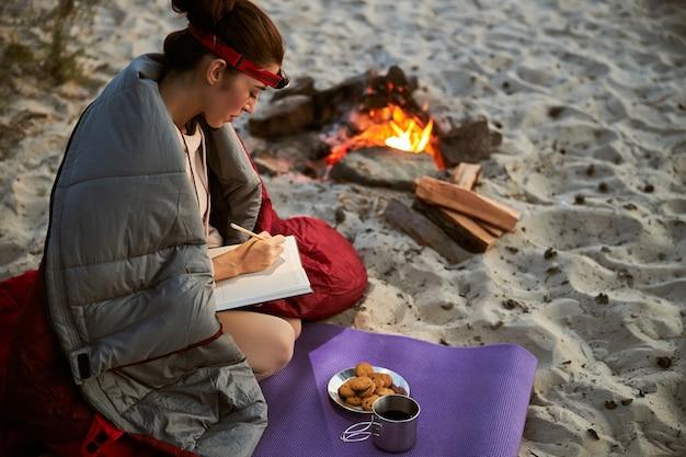 焚き火の近くのヨガマットに座って日記を書く寝袋に包まれた魅力的な若い女性