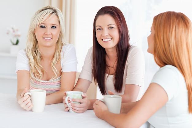カップのあるテーブルに座っている魅力的な若い女性