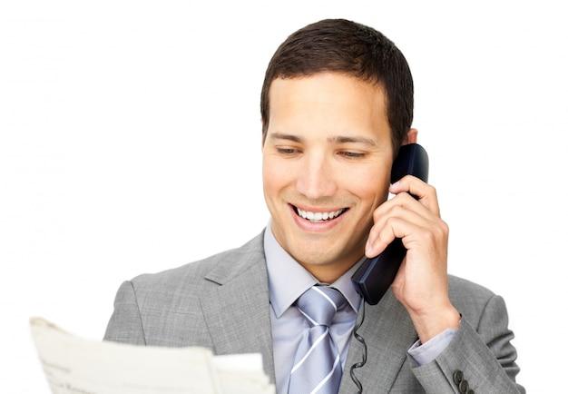 新聞を持って電話でcharsmaticのビジネスマン