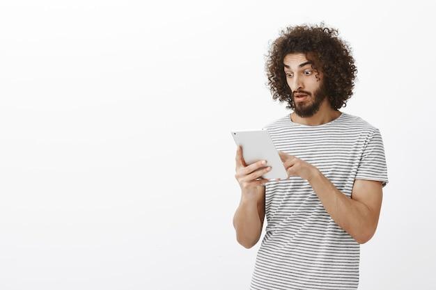 Carta della compagnia alzata inaspettatamente. studente maschio bello scioccato e contento con barba e capelli ricci, mascella cadente durante lo scorrimento dei feed di notizie nella tavoletta digitale