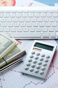 Диаграммы и гистограммы, деньги, клавиатура компьютера и калькулятор на рабочем столе.