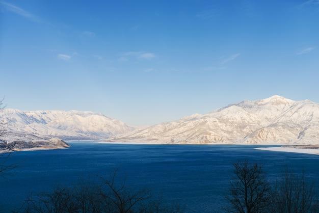 天山山脈の雪をかぶった山頂に囲まれた、ウズベキスタンの晴れた冬の日に青い水が流れるチャルヴァク貯水池
