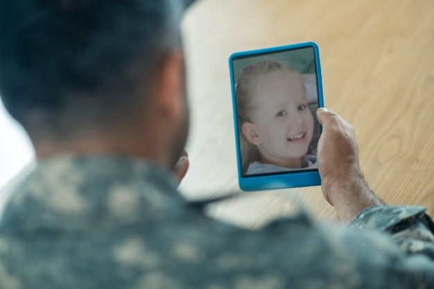 Chat with daughter. close up of serviceman holding tablet while having video chat with