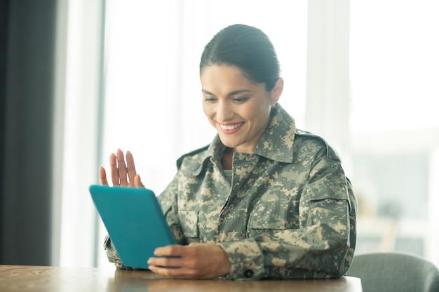 家族とチャットします。タブレットで家族とビデオチャットをしている軍隊で奉仕する美しい女性