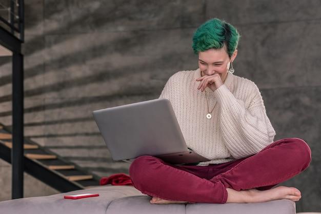 友達とチャット。友達とビデオチャットをしながら笑う緑髪の陽気な女性