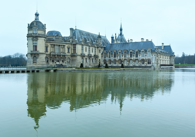 Chateau de chantilly (france). the petit chateau built in 1560 (on right, architect  jean bullant) and grand chateau rebuilt in 1870 s (on left, architect honore daumet).