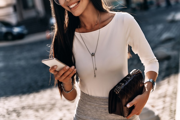 Chating with friends. close-up of attractive young woman holding smart phone and smiling while standing outdoors