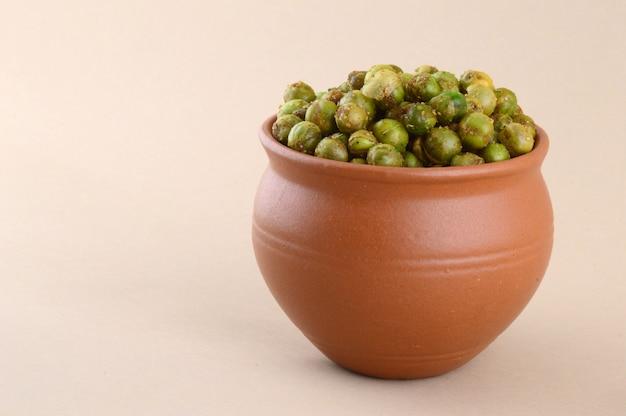 グリーンピースの炒め{chatpata matar}インドのスナック。土鍋で塩漬けのグリーンピースを乾燥させます。