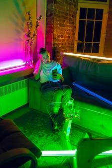 Болтаем. кинематографический портрет стильной женщины в неоновой подсветке интерьера. тонирован как киноэффекты, яркие неоновые цвета. кавказская модель с помощью смартфона в красочные огни в помещении. молодежная культура.