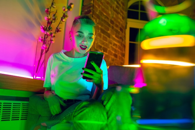 Chatting. cinematic portrait of stylish woman in neon lighted interior. toned like cinema effects, bright neoned colors. caucasian model using smartphone in colorful lights indoors. youth culture.