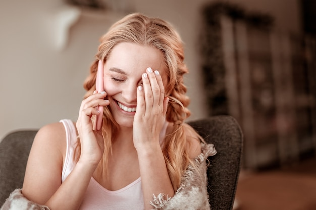 電話でチャット。友人との陽気な対話のために彼女の顔を閉じる2つの三つ編みで明るい髪の女性を冗談で言う