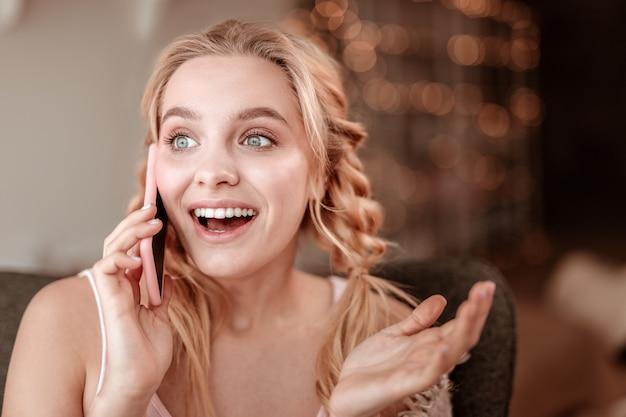 スマートフォンでチャット。大きく開いた青い目をした明るい髪の美しい女性は、対話中に非常に表現力豊かです