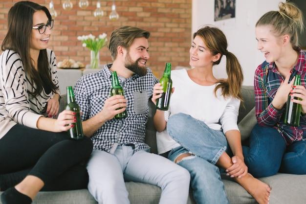 Chatting people having beer on sofa