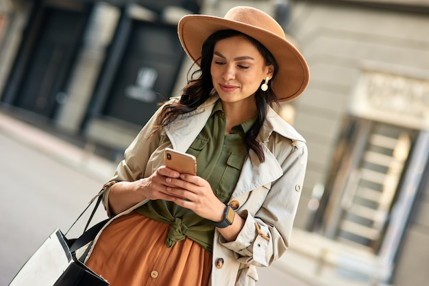 Chatting with friend young beautiful stylish woman wearing autumn coat and hat using her smartphone
