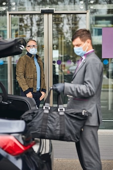 Chauffeur holding his client baggage with one hand