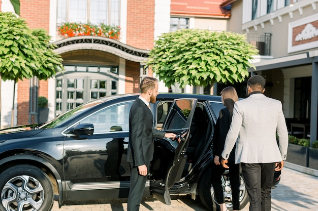 Chauffeur man opening car door for business couple, caucasian woman and african man, side view. business trip by car.