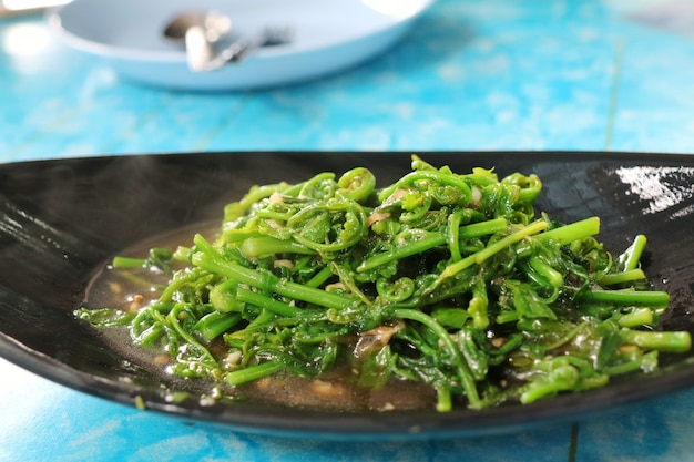 Chayote leaves in oyster sauce in black plate. food and object concept.