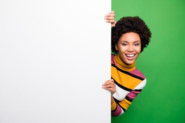 安い広告!ニュースウェアカジュアルストライプセーターの大きな白い空のスペースのポスターを提示する美しい暗い肌の波状の女性の興奮した気分の写真