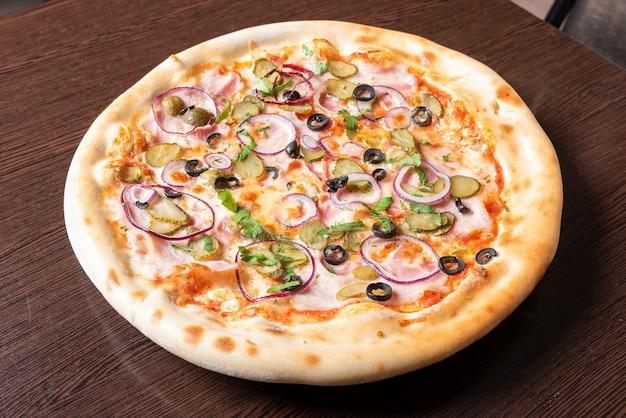 Дешевая пицца с ветчиной, луком, маринованными огурцами и оливками. для любых целей.