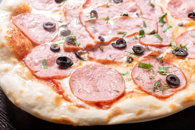 Дешевая пицца с пепперони, ветчиной, оливками и зеленью. для любых целей.