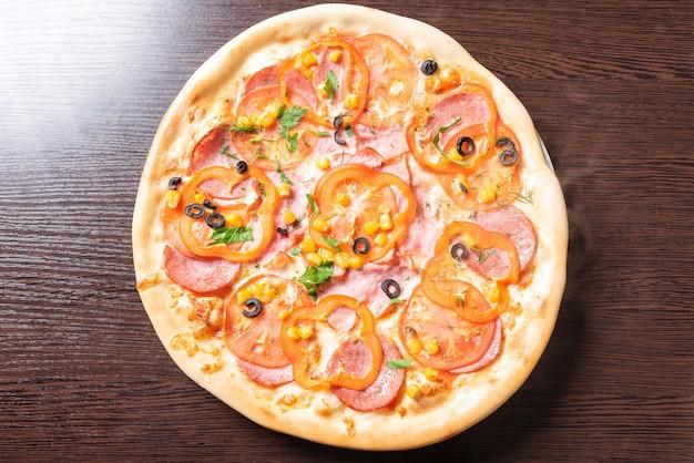Дешевая пицца с помидорами, перцем, ветчиной и оливками. для любых целей.
