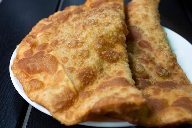 チェブレキ-プレートに肉と玉ねぎを添えた揚げパイ。多くのチュルク人とモンゴル人の伝統的な料理、クローズアップ