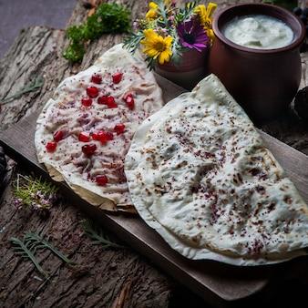 クローズアップchebureks kutab揚げたchebureks、ザクロ、チーズ、ハーブ、ダーク木製テーブル
