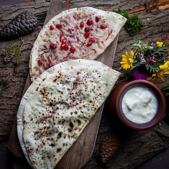 トップビューchebureks kutab揚げたchebureks、ザクロ、チーズ、ハーブ、肉のソース添え