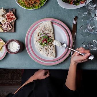トップビューchebureks kutab揚げたchebureksザクロ添え、別の食事、ナイフ、フォーク、グラス水平の添えられたテーブルのソース