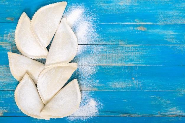 青い木製のテーブルの上に小麦粉で揚げたchebureksではありません。伝統的なチュルクモンゴル料理。冷凍半製品。碑文の空き容量。