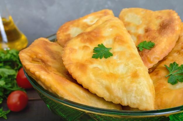 木製のテーブルにジューシーなゴールデンchebureks。伝統的なチュルクモンゴル料理。屋台の食べ物。ビストロ。
