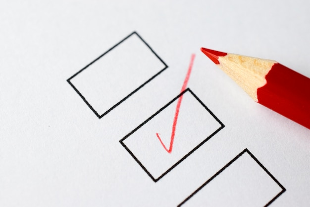 Check boxes on a white paper with red pencil