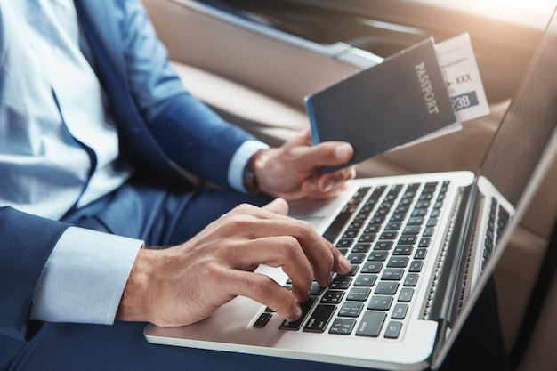 Check in cropped image of young businessman in formal wear working on laptop and holding