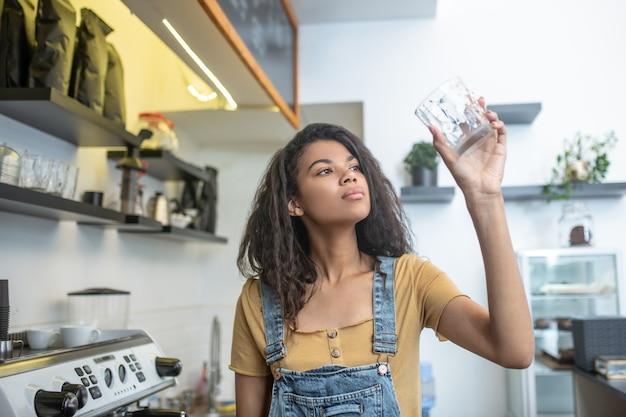 Проверить на чистоту. внимательная молодая взрослая женщина, глядя на стекло в поднятой руке, стоя возле кофеварки в кафе