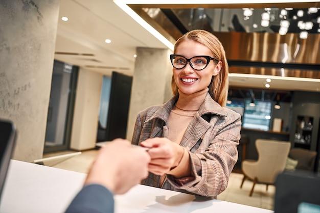 Размещение в отеле после длительной командировки. крупный план женщины при регистрации в отеле на стойке регистрации или на стойке регистрации, которой выдают ключ-карту.