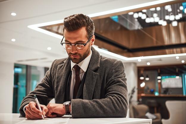 Размещение в отеле после длительной командировки. мужчина в отеле регистрируется на стойке регистрации или в офисе и заполняет свой профиль