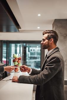 Размещение в отеле после длительной командировки. мужчина в отеле регистрируется на стойке регистрации или в переднем офисе, получая ключ-карту