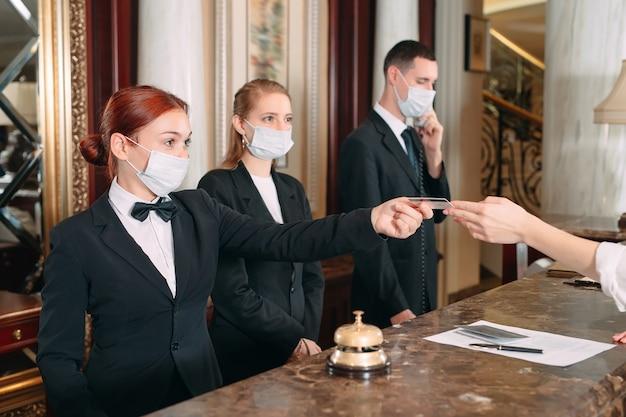 ホテルにチェックインします。コロナウイルスに対する予防措置として医療用マスクを着用したホテルのカウンターの受付係。ホテルでチェックインをしている出張の若い女性