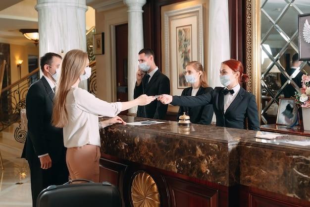 호텔 체크인. 바이러스에 대한 예방 조치로 의료 마스크를 착용 한 호텔의 카운터에서 접수. 호텔에서 체크인을 하 고 출장에 젊은 여자