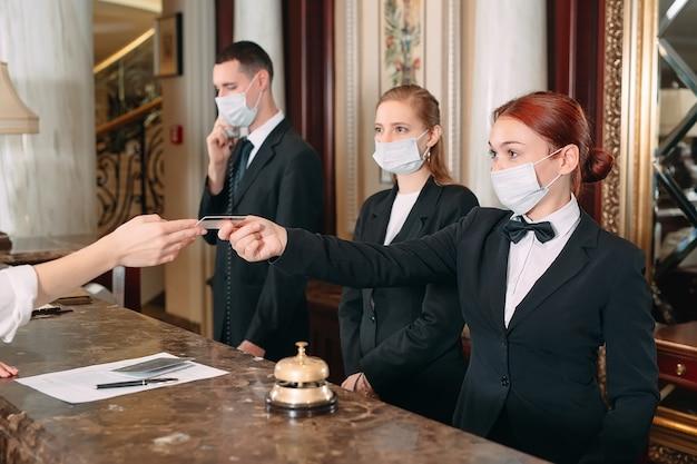 호텔 체크인. 바이러스에 대한 예방 조치로 의료 마스크를 착용 한 호텔의 카운터에서 접수. 출장 호텔에서 체크인 하 고 젊은 여자
