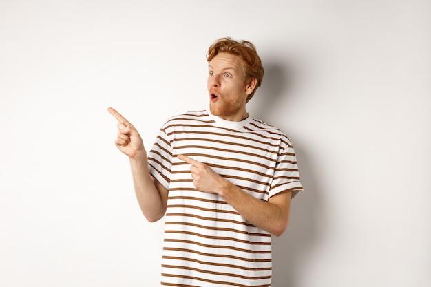見てみな。白い背景の上に立って、すごい、と言って、プロモーションバナーを指して左を見て驚いた赤毛の男。